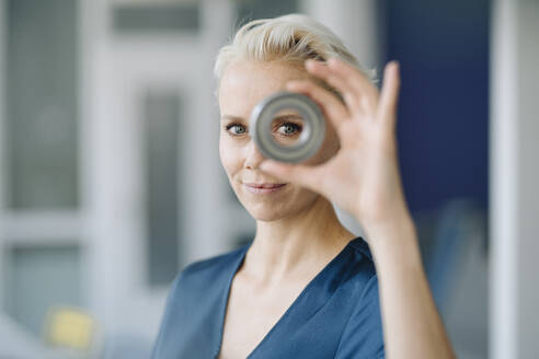 Close-up of confident businesswoman looking through object in office - KNSF08598
