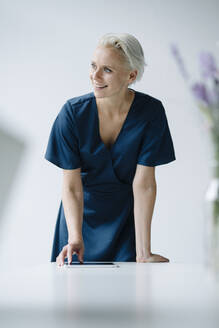 Smiling businesswoman with digital tablet on desk looking away in office - KNSF08619