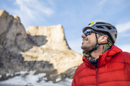 Smiling side view portrait of mountain climber below summit. - CAVF88792