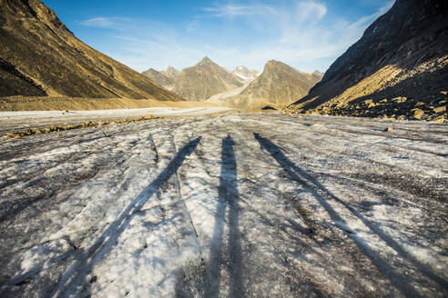 Shadows of three explorers on a glacier in the mountains. - CAVF88813