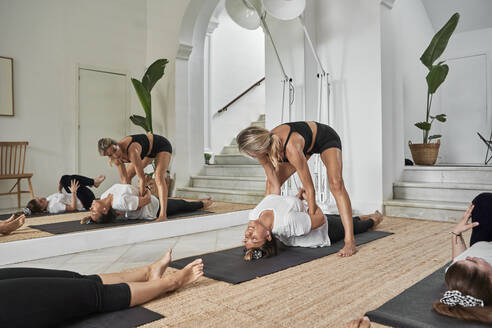 Yoga instructor assisting woman in exercising at health club - VEGF02900