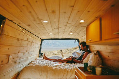 Young man on bed with laptop in camper van in northern California. - CAVF88864