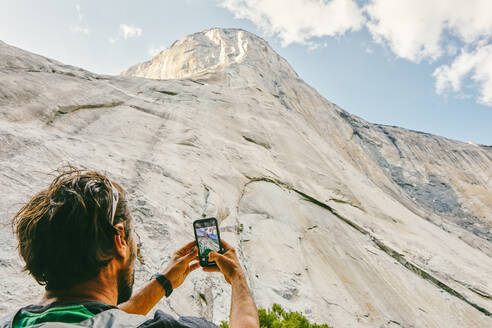 Young man taking picture of El Capitan Mountain in Yosemite Park. - CAVF88879