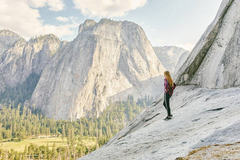 Young woman standing on El Capitan Mountain looking out to Yosemite - CAVF88882