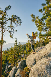 Young woman taking a picture of sunset over Lake Tahoe. - CAVF88885