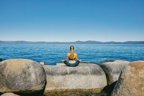Young woman practicing yoga on Lake Tahoe in northern California. - CAVF88891