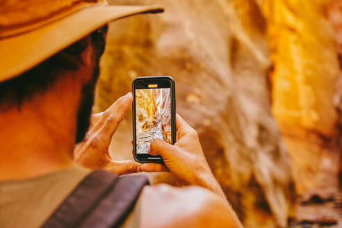Young man wearing hat taking picture of slot canyons in Kanarra Falls - CAVF88906