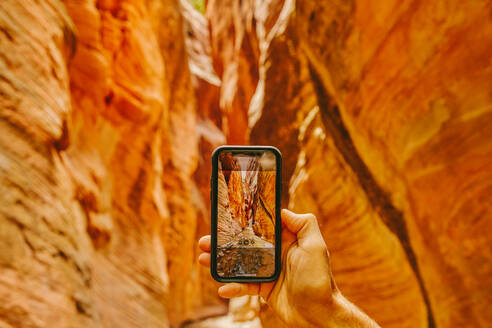 Young man's hand taking picture of slot canyons in Kanarra Falls - CAVF88909