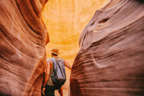 Young man exploring narrow slot canyons in Escalante, during summer - CAVF88915
