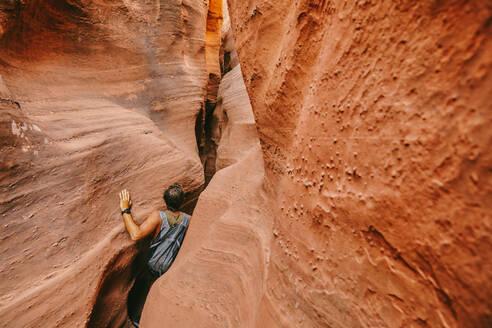 Young man exploring narrow slot canyons in Escalante, during summer - CAVF88927