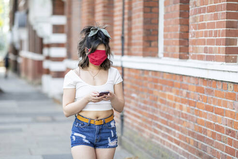Young woman's face covered with mask using smart phone while standing in city - WPEF03346