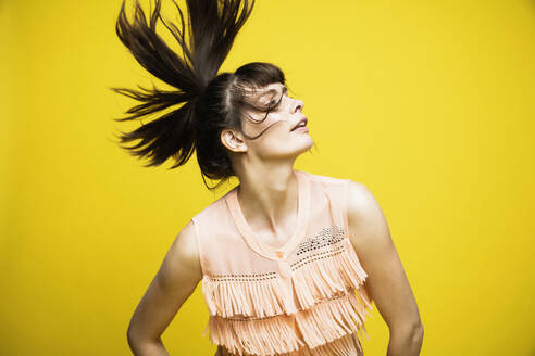 Fashion model tossing hair while standing against yellow background - DHEF00394