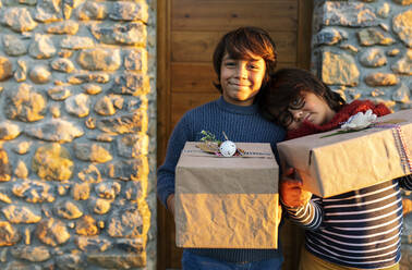 Brothers holding Christmas presents while standing against house - VABF03458