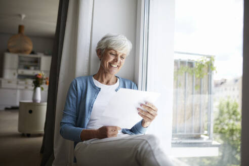 Senior woman reading letter happily while sitting on window at home - RBF07790