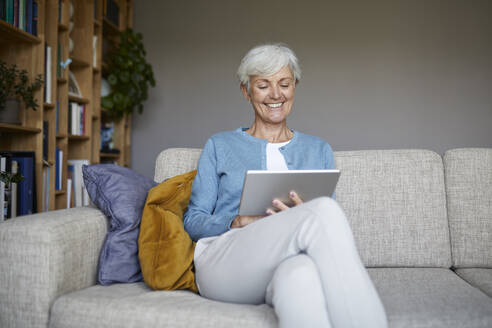 Smiling senior woman using digital tablet while sitting at home - RBF07796