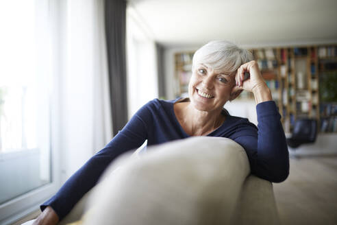 Smiling senior woman relaxing while sitting on sofa - RBF07823