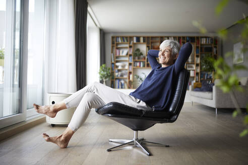 Happy senior woman with hands behind head sitting on chair at home - RBF07829