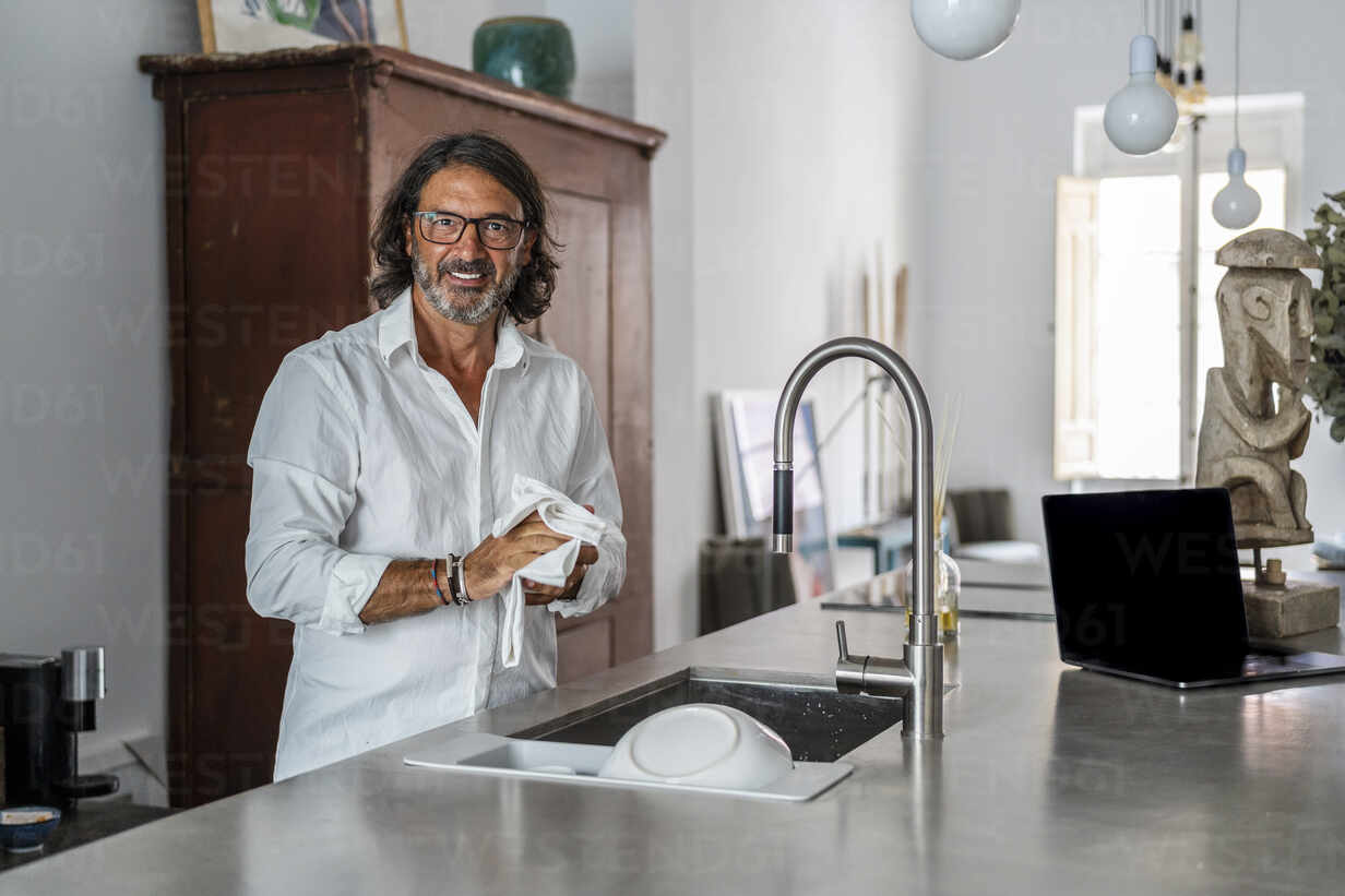 Smiling Man Cleaning Crockery While Standing By Sink In Kitchen Stockphoto