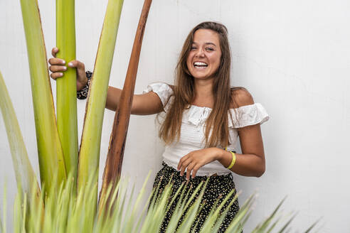 Smiling woman holding plant while standing against wall - DLTSF01150