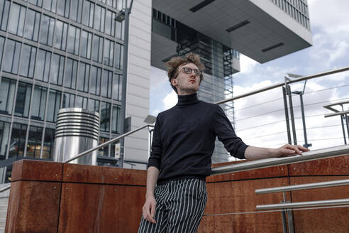 Thoughtful young man standing by railing against building in city - OGF00566