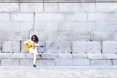 Guitarist playing guitar while sitting against concrete wall - JCMF01395