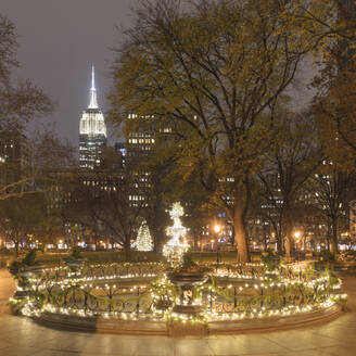 USA, New York, New York City, Madison Square Park with Christmas lights, Empire State Building in background - AHF00061