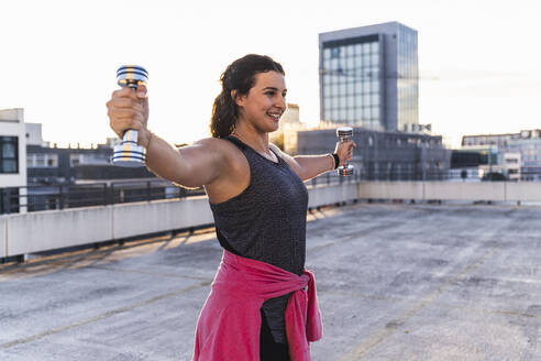 Smiling young woman with arms outstretched lifting dumbbells on terrace at sunset - UUF21412