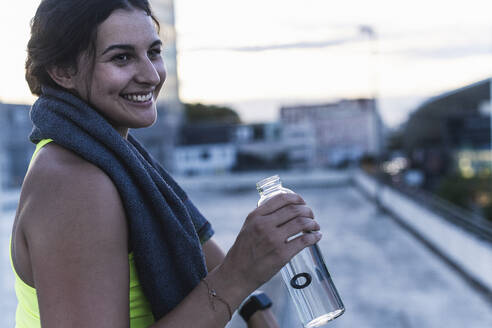 Close-up of smiling young woman holding water bottle looking away while sitting on terrace - UUF21421