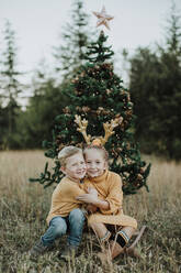 Smiling siblings embracing while sitting by Christmas tree on grassy land - GMLF00596