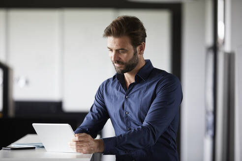Businessman using digital tablet while standing at desk in office - RBF07889