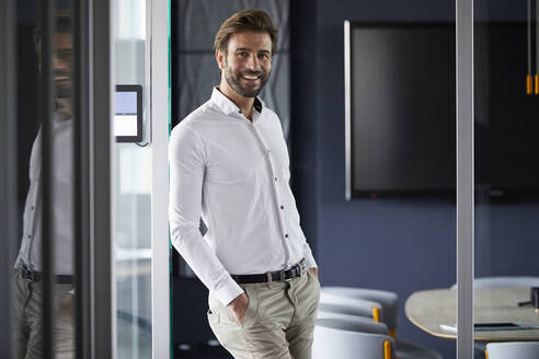 Smiling businessman leaning on glass wall in office - RBF07898