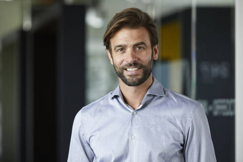 Smiling businessman standing against glass wall in office - RBF07913