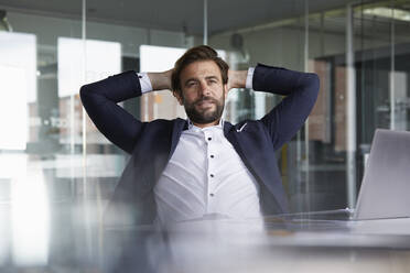 Thoughtful businessman with hands behind head sitting in office - RBF07919