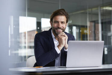 Smiling businessman using laptop while sitting on chair in office - RBF07922