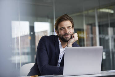 Businessman with head in hands leaning on desk while sitting in office - RBF07925