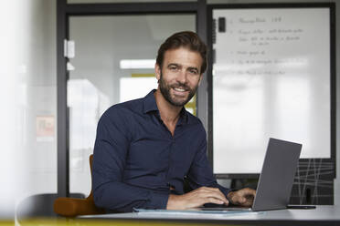 Smiling man working on laptop while sitting by desk in office - RBF07928