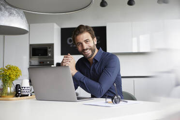 Smiling man using laptop while sitting at cafeteria - RBF07931