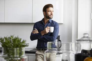 Man drinking coffee standing at cafeteria in office - RBF07934