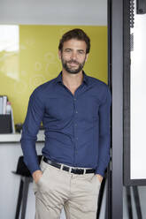 Businessman with hands in pockets leaning on wall at office - RBF07937