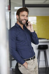 Businessman talking on phone while leaning on wall in office - RBF07940