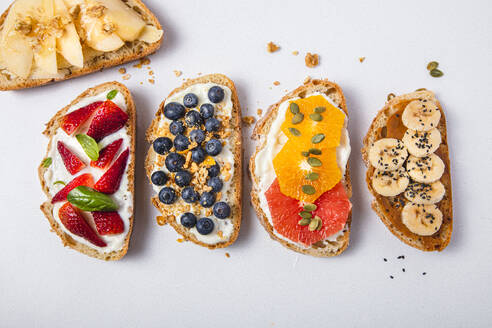 Studio shot of five slices of bread with fresh fruits - FLMF00296