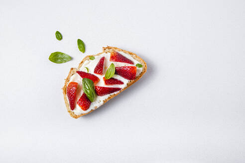 Studio shot of slice of bread with strawberries and basil - FLMF00299