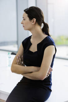 Thoughtful businesswoman with arms crossed sitting on conference table in board room - BMOF00405