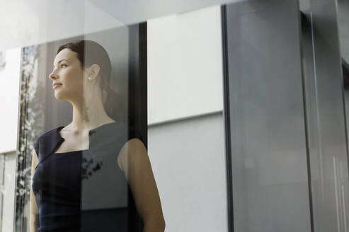 Thoughtful female entrepreneur looking away while standing in office seen through glass door - BMOF00411