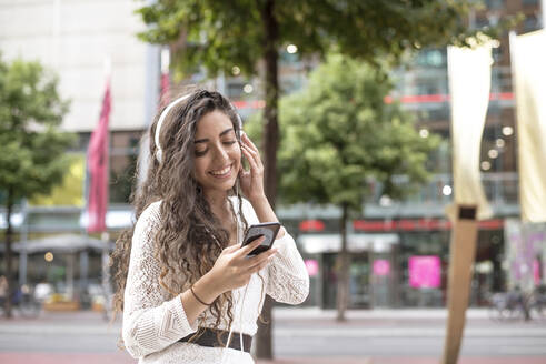 Smiling young woman listening music and using smart phone while standing in city - BFRF02288