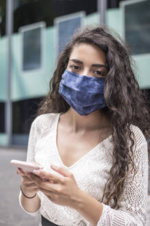 Close-up of woman wearing face mask using smart phone while standing in city - BFRF02297