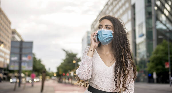 Woman wearing mask talking over mobile phone while standing in city - BFRF02306
