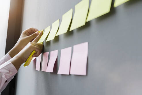 Hands of businesswoman sticking adhesive notes on wall in office - BMOF00419