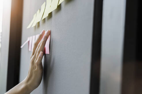 Close-up of female entrepreneur hand sticking adhesive notes on wall in office - BMOF00425