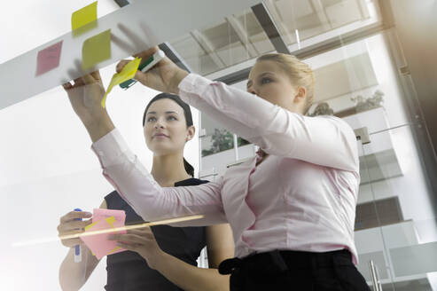 Female colleagues sticking adhesive notes on glass wall in office - BMOF00428
